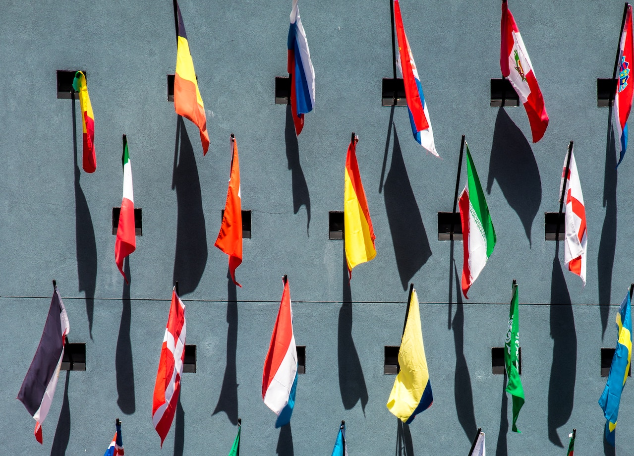 photo of assorted-color nation flags on wall during daytime